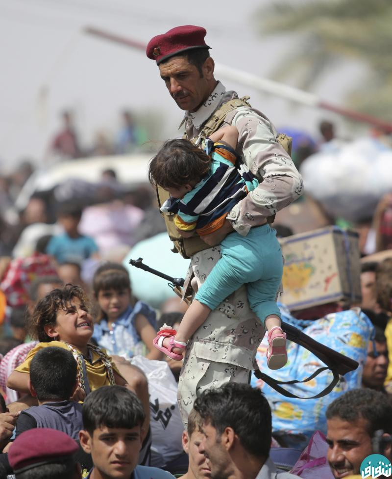An Iraqi soldier carries a child as displaced Sunni people, who fled the violence in the city of Ramadi, arrive at the outskirts of Baghdad